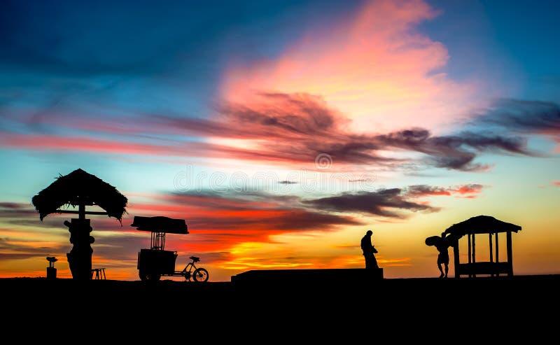 La puesta del sol tropical vibrante con la paja remató las chozas de la playa silueteadas contra el cielo imagen de archivo libre de regalías