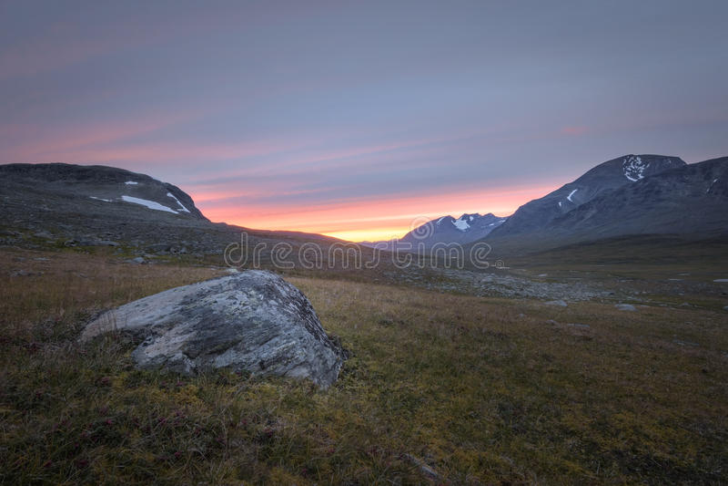 La puesta del sol vibrante sobre el Sarek rocoso aclara Suecia imagenes de archivo