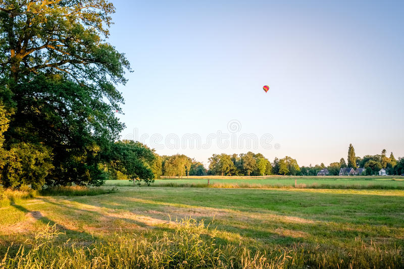 La puesta del sol y el balón de aire sobre verano holandés ajardinan Delden, Twente imagenes de archivo
