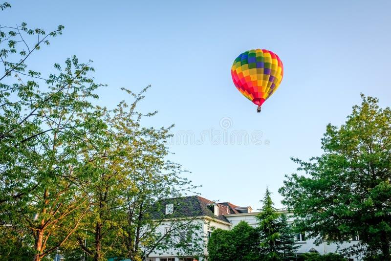 La puesta del sol y el balón de aire sobre verano holandés ajardinan Delden, Twente fotografía de archivo