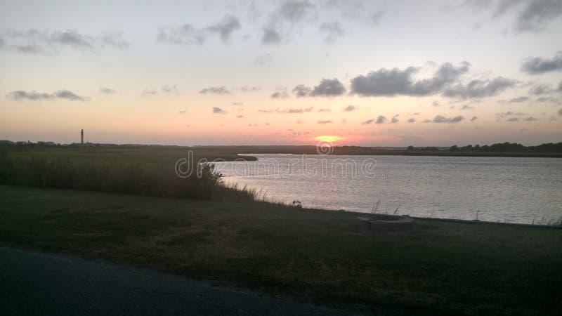 La puesta del sol y el faro imagen de archivo
