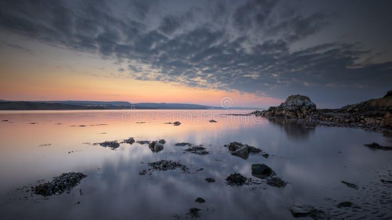 La puesta del sol y la marea baja en los marrones aúllan foto de archivo libre de regalías