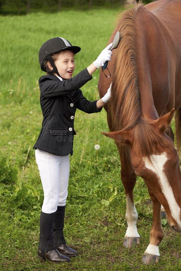 La puleggia tenditrice della bambina assiste e spazzolando il suo cavallo immagine stock