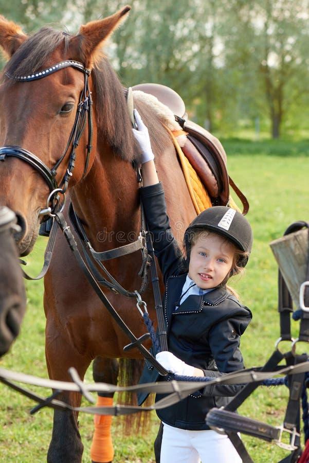 La puleggia tenditrice della bambina assiste e spazzolando il suo cavallo fotografia stock
