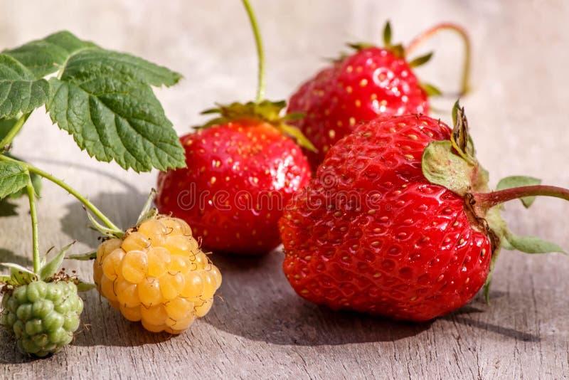La puntilla de frambuesas amarillas y las fresas maduras rojas no son tabla de madera gris imagen de archivo libre de regalías