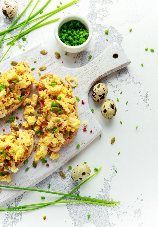 La quaglia casalinga ha rimescolato le uova su pane tostato croccante, pane con la cipolla verde, erba cipollina sul bordo bianco fotografie stock libere da diritti