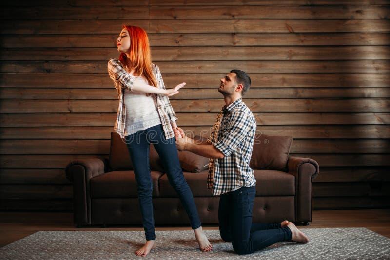 La querelle de famille, homme sur ses genoux fait des excuses photo stock