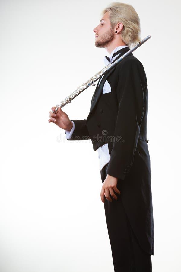 La queue de pie de port de flûtiste masculin tient la cannelure photo stock