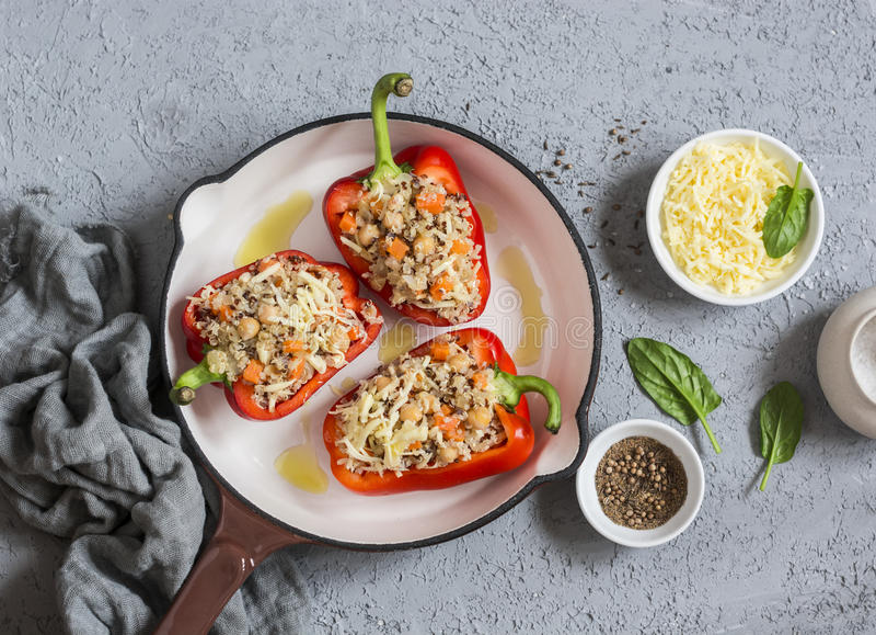 La quinoa cruda ha farcito i peperoni dolci in una padella del ghisa Vista superiore Alimento sano e vegetariano immagine stock