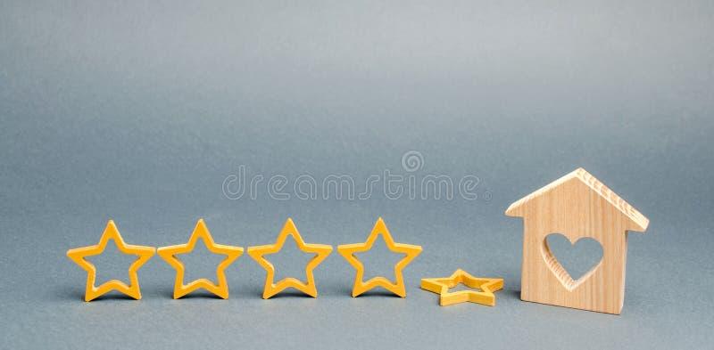 La quinta estrella de la ca?da cerca de una casa de madera miniatura El concepto de hotel o de restaurante de clasificaci?n que c fotografía de archivo