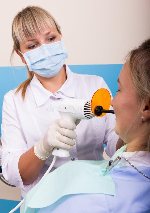 La réception était au dentiste féminin que Doctor examine la cavité buccale sur la carie dentaire image libre de droits