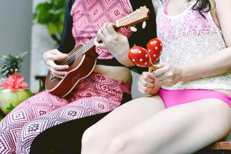 La réception au bord de la piscine de détente d'heure d'été, amies ont plaisir à jouer et chanter par la piscine des vacances photos stock