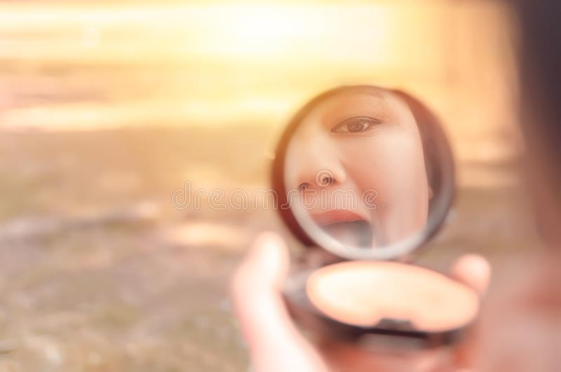 La réflexion d'une jeune dame mettant sur elle composent photo stock