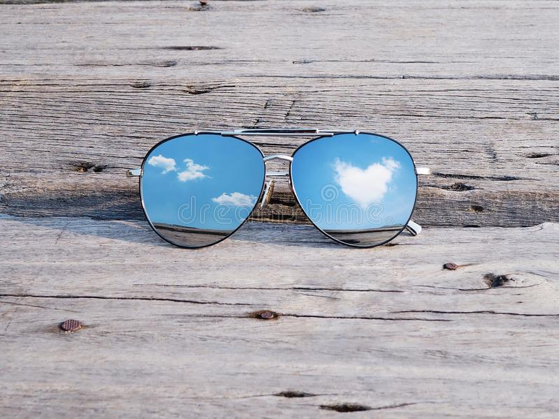 La réflexion du coeur de ciel bleu et de nuages forment dans des lunettes de soleil image stock