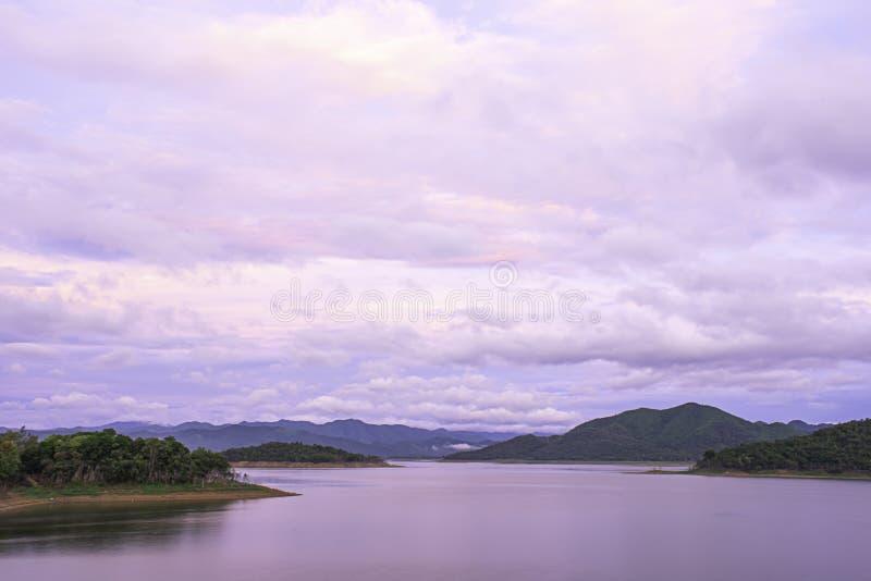 La réflexion du Sun et les nuages sur la montagne et l'eau de fond de ciel au barrage de Kaeng Krachan dans le phetchaburi, Thaïl photos stock