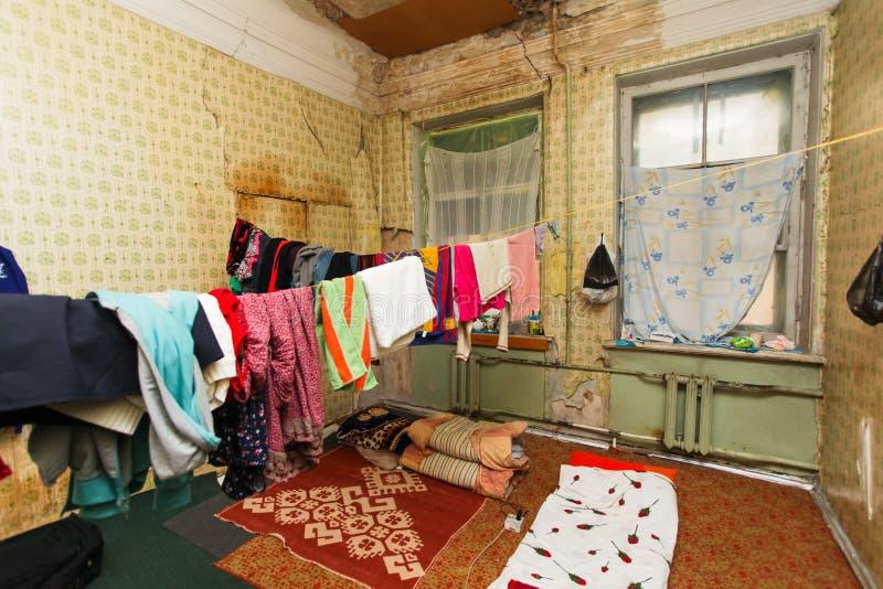 La région de sommeil pour des vêtements de ` de réfugié et de réfugiés est séchage de sur la corde dans l'appartement provisoire images stock
