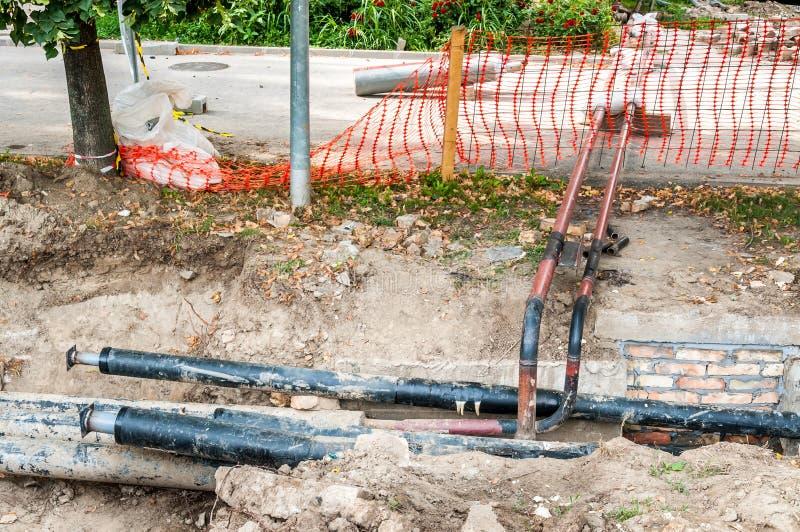 La réparation et la reconstruction de canalisation de chauffage urbain parallèles avec la rue avec le filet de sécurité orange de photographie stock libre de droits