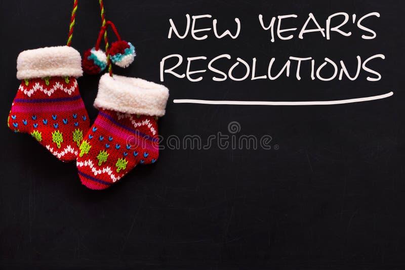 La résolution de nouvelle année de mot écrite sur le tableau noir avec mitaines photos stock