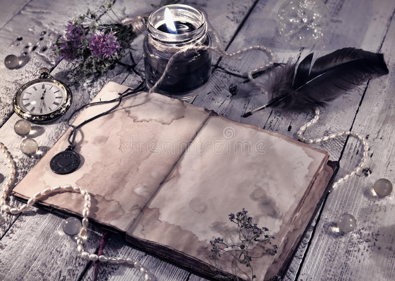 La rétro dénommée toujours vie avec le vieux journal intime, la bougie noire et les objets mystiques photographie stock