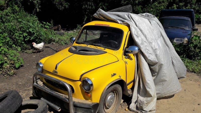La rétro voiture minuscule jaune se tient dans la cour image libre de droits