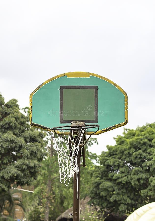 La r?paration cass?e de cercle de basket-ball fonctionnent temporairement l'arbre trouble et le ciel de fond photographie stock