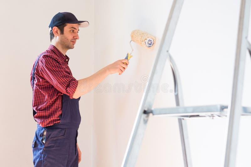 La r?paration, la r?novation et le concept ? la maison avec la peinture de l'homme murent ? la maison images stock