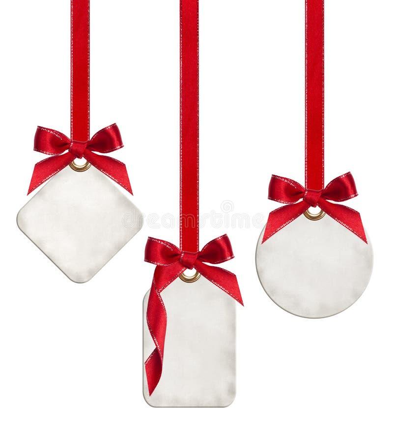 La raccolta delle etichette in bianco del regalo legate con il nastro rosso del raso si piega fotografia stock libera da diritti