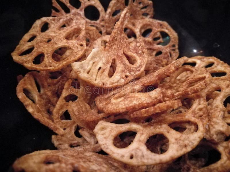 La racine croustillante frite d'or de lotus ébrèche dans la cuvette noire photos libres de droits