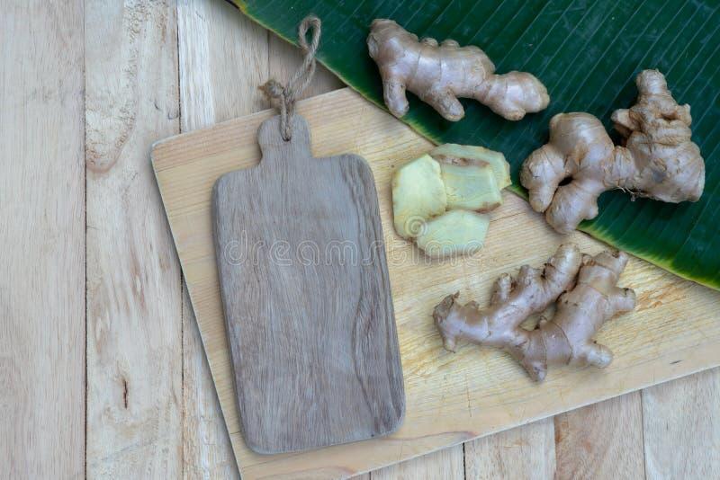 La racine de gingembre et le gingembre frais ont découpé en tranches sur le fond vert de feuille sur le fond en bois de table, co images libres de droits