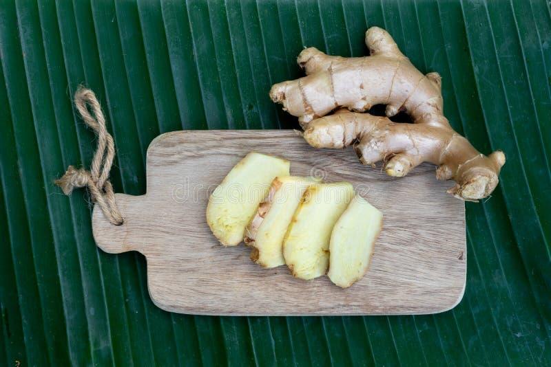 La racine de gingembre et le gingembre frais ont découpé en tranches sur le fond vert de feuille sur le fond en bois de table, co photos libres de droits