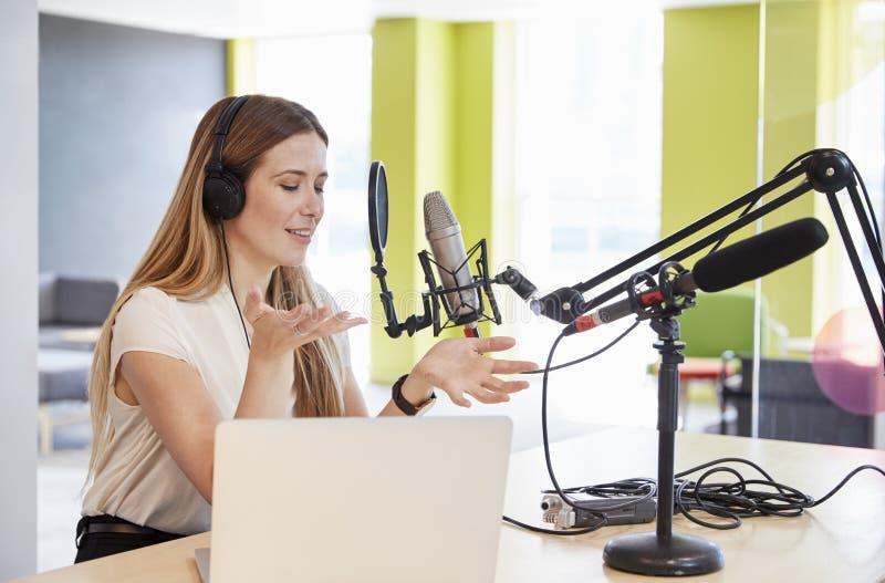 La radiodiffusion de jeune femme dans un studio faisant des gestes, se ferment  photo stock
