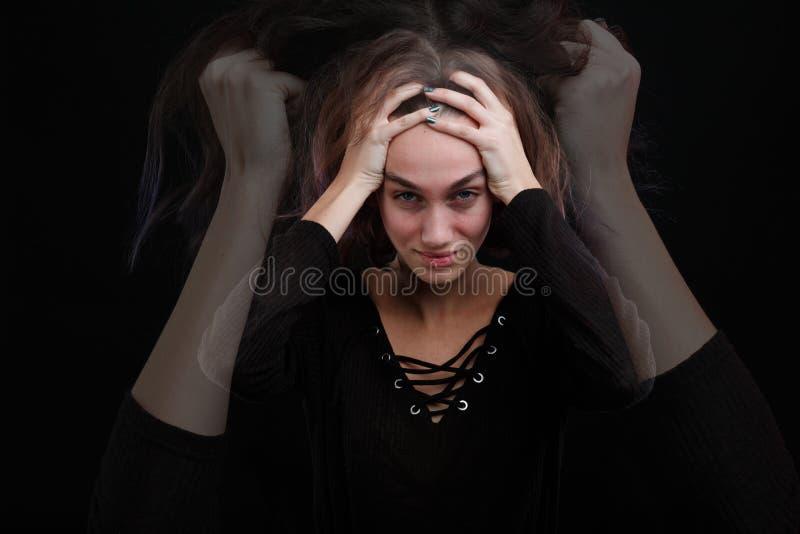 La ragazza è alta sulla testa su un fondo nero immagine stock