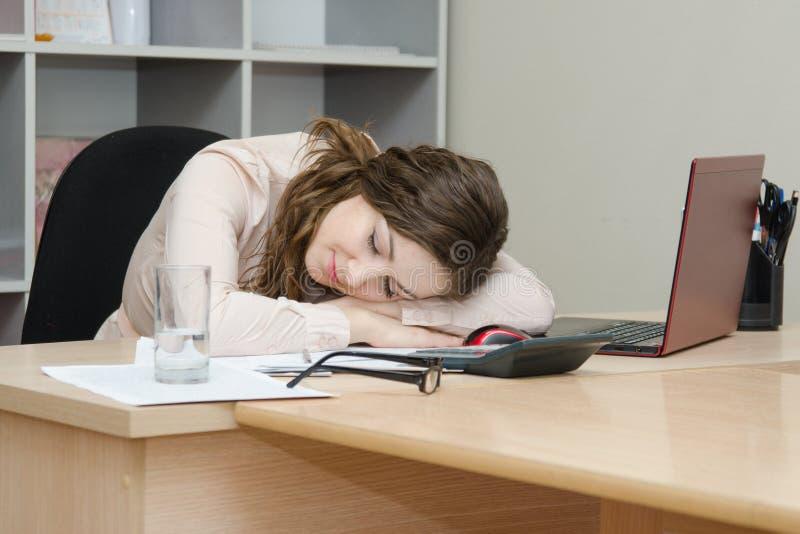 La ragazza è caduto addormentato al suo computer portatile nell'ufficio immagine stock libera da diritti