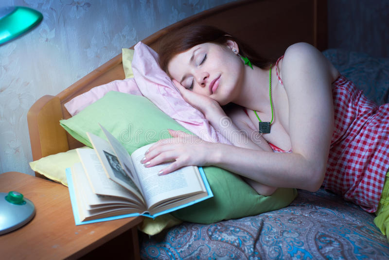 La ragazza è caduto addormentato con un libro fotografie stock libere da diritti