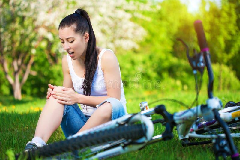 La ragazza è caduto dalla bici in un parco verde fotografie stock libere da diritti