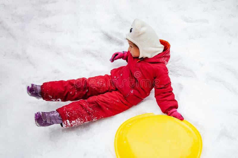 La ragazza è caduto nella guida della neve sulla slitta fotografia stock