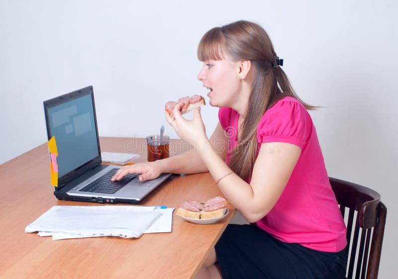 La ragazza è dietro il computer portatile fotografia stock libera da diritti