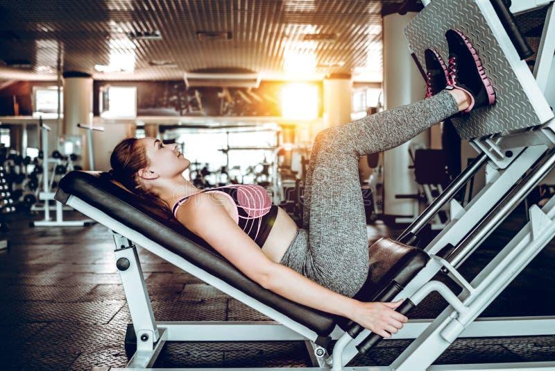 La ragazza è impegnata nell'allenamento di forma fisica con la stampa della gamba del simulatore alla palestra fotografia stock libera da diritti