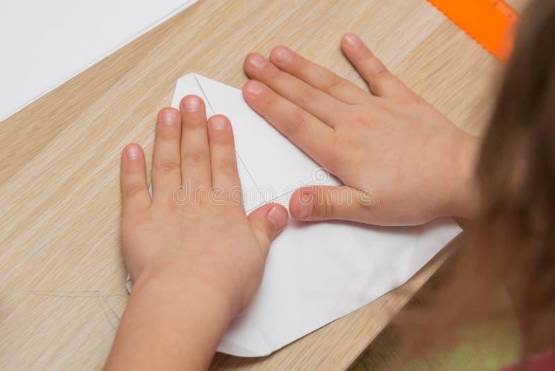 La ragazza è impegnata in origami, fa l'aeroplano di carta fotografia stock libera da diritti