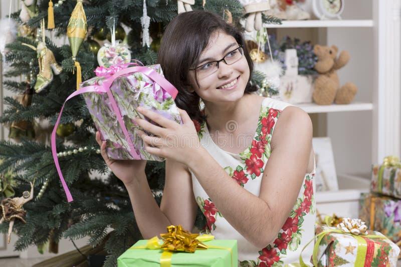La ragazza è intrigata con il regalo di Natale fotografia stock