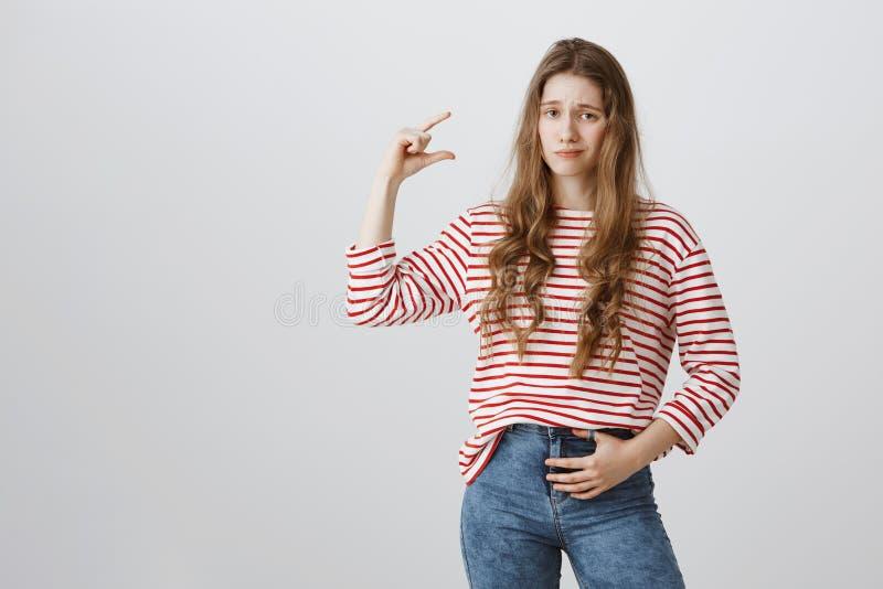La ragazza è non impressionata con l'importo o la forma Ritratto della donna caucasica indifferente dispiaciuta con da fare rizza fotografia stock libera da diritti