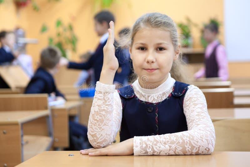 La ragazza è un allievo della mano in aumento della scuola elementare mentre si siede allo scrittorio fotografia stock