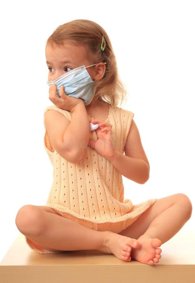 La ragazza è in un medico con un termometro. immagini stock libere da diritti