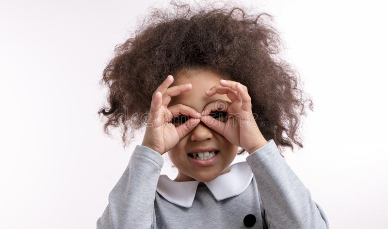 La ragazza abbastanza africana sta utilizzando le sue dita per formare i sungglasses immagine stock libera da diritti