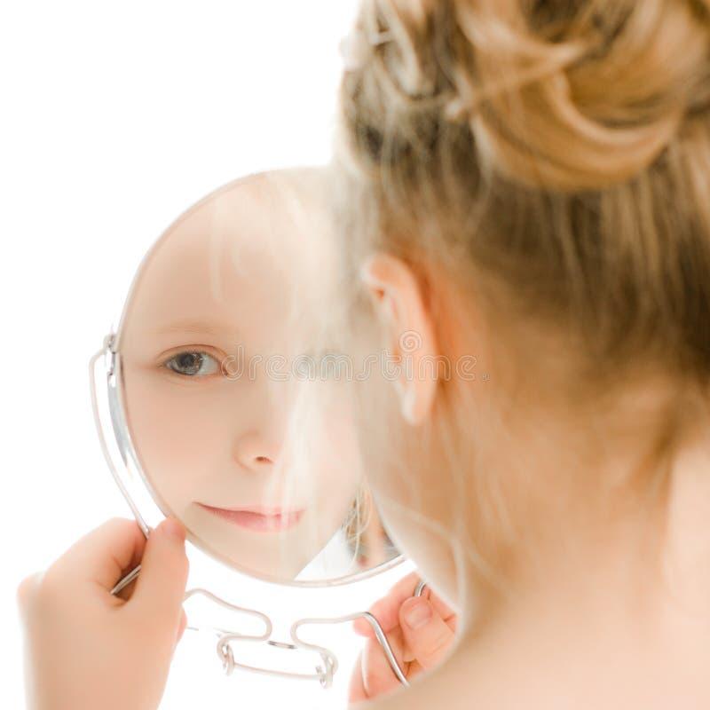 La ragazza abbastanza bella guarda nello specchio. immagini stock