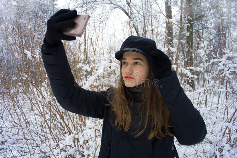 La ragazza abbastanza teenager di modo fa il ritratto del selfie nella foresta nevosa dell'inverno fotografia stock