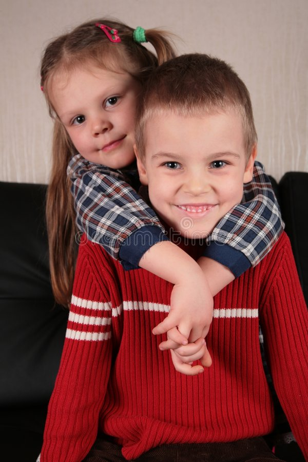 La ragazza abbraccia il ragazzo per il collo sul sofà fotografia stock