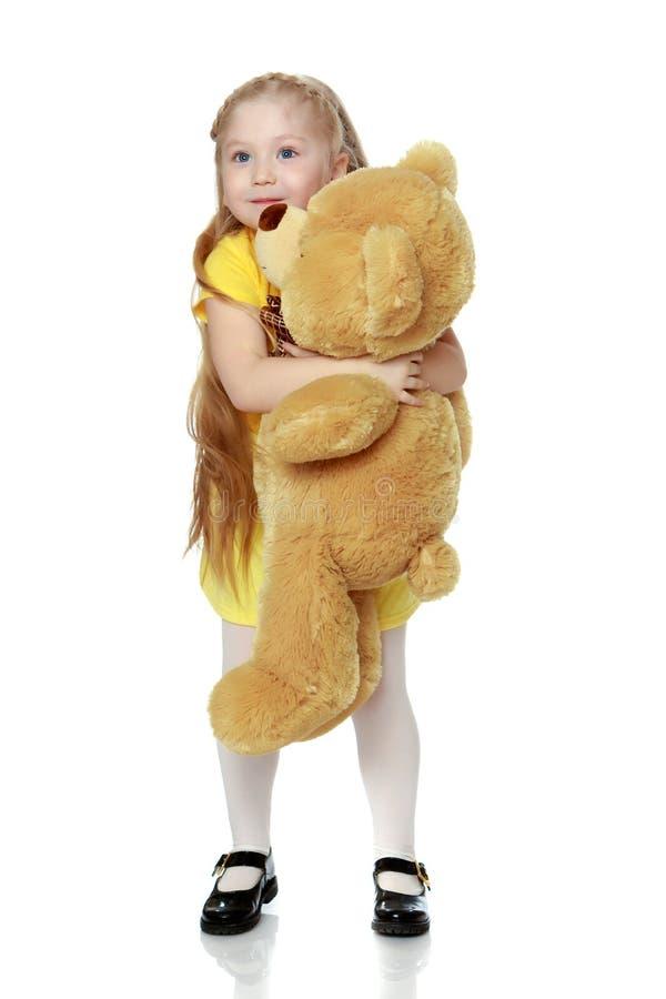 La ragazza abbraccia un grande orsacchiotto fotografia stock