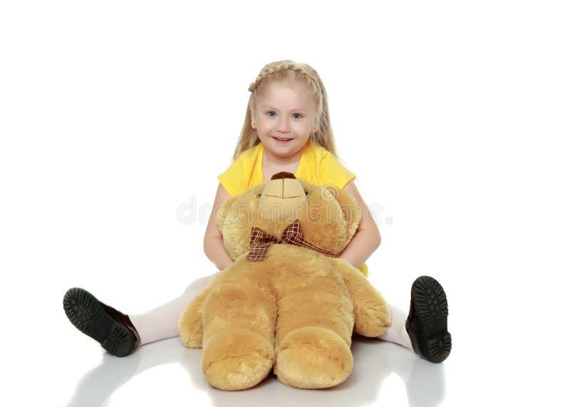 La ragazza abbraccia un grande orsacchiotto fotografie stock