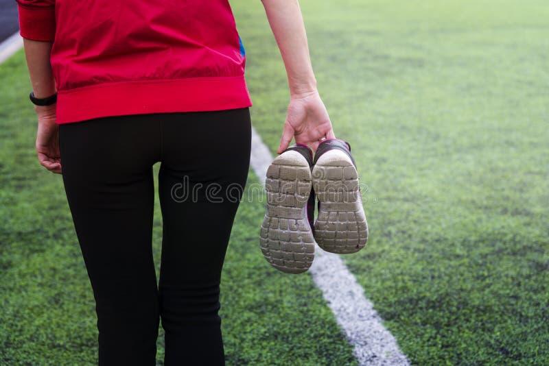 La ragazza in abiti sportivi cammina attraverso lo stadio e tiene le scarpe da tennis in sue mani fotografie stock libere da diritti